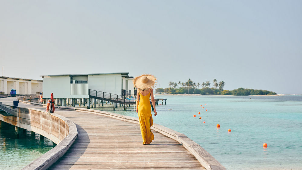 Woman in dress walking on tropical beach boardwalk. Summer vacation at Maldives.